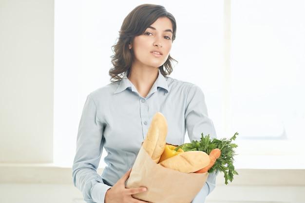 食料品のパッケージを持つブルネット主婦ライフスタイルスーパーマーケット