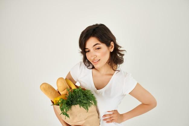 食料品のスーパーマーケットの配達のパッケージを持つブルネット。高品質の写真