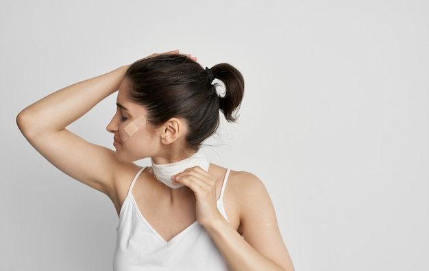 Brunette with a bandaged neck holding her head health problems