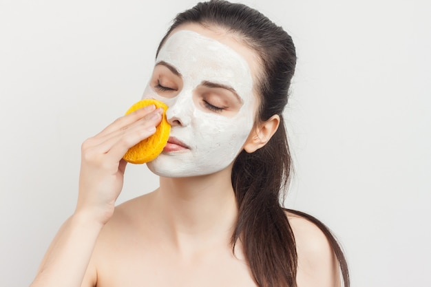 Brunette with bare shoulders face mask sponges in hands