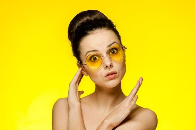 Брюнетка с открытыми плечами держит руки возле лица с чистой кожей в желтых очках. фото высокого качества