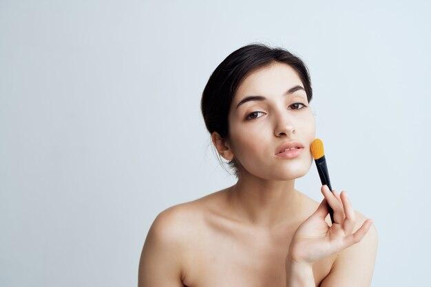 Брюнетка с открытыми плечами для макияжа лица