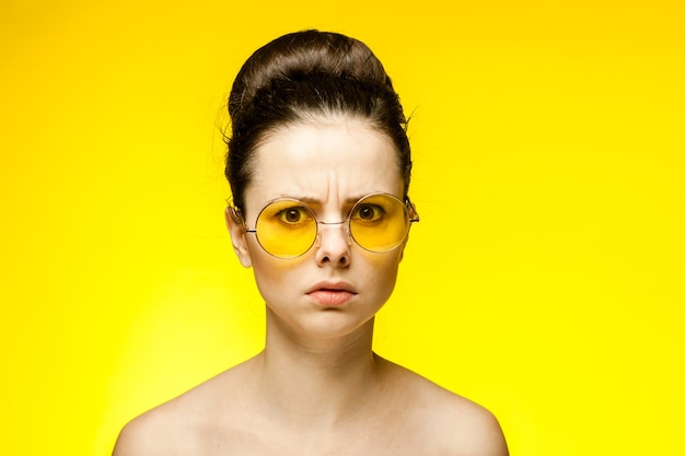 黄色いメガネを身に着けている裸の肩を持つブルネットクロップドビュー孤立した背景感情ファッション