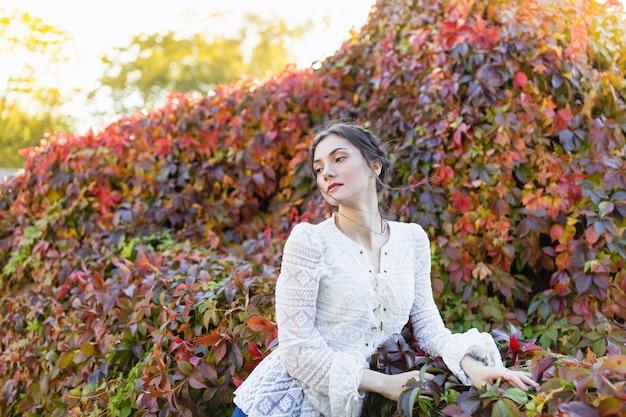 Брюнетка с косами в стильной винтажной белой кружевной блузке с длинным рукавом в осеннем парке