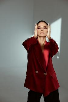 顔の赤いジャケットのファッションの近くに明るい化粧の手でブルネット。高品質の写真