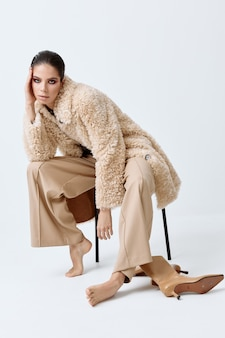 Brunette with bright makeup on her face beige coat fashionable clothes barefoot sitting on a chair.