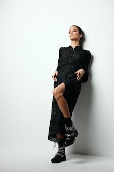 黒のドレスファッショナブルなモダンな服の孤立した背景の明るい化粧とブルネット