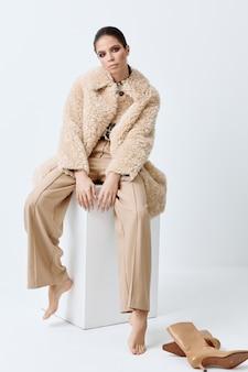 彼女の顔に明るい化粧をしたブルネットベージュのコートのファッショナブルな服。
