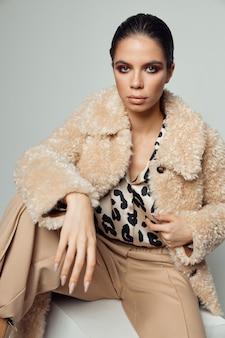 彼女の顔に明るい化粧をしたブルネットヒョウシャツファッション服秋のスタイル。