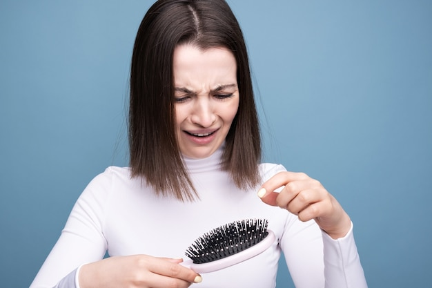 Brunette with a comb in her hands in shock from hair loss on blue background