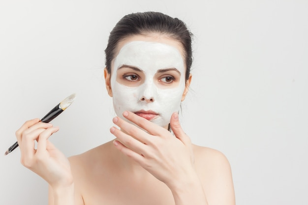 Brunette with cream face mask skin care brush applying makeup.
