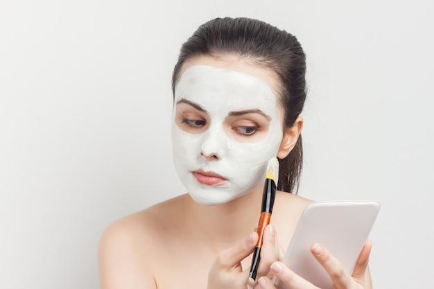 Brunette with cream on her face brush in hands applying cream.