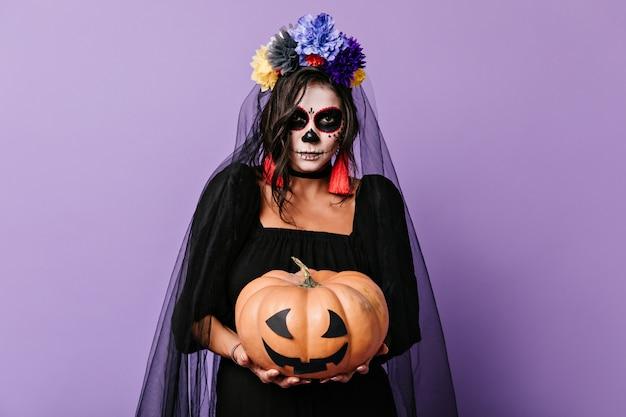 Брюнетка с фейс-артом мексиканского черепа держит украшенную тыкву. фото в помещении молодой девушки с короной из цветов.