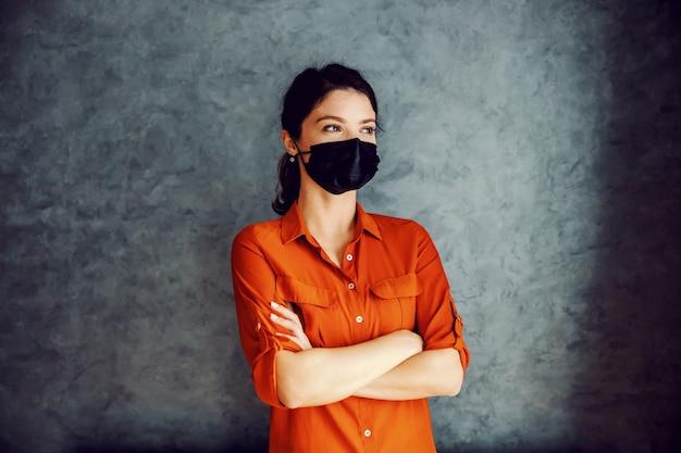 腕を組んで立っているフェイスマスクとブルネット。あなたはコロナが通過することを信じなければなりません。