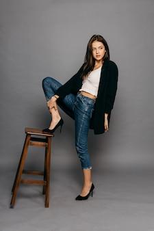 Брюнетка с длинными волосами в куртке и джинсах поставила ногу на спинку стула. фото высокого качества