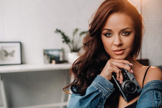 A brunette with long hair poses in a studio sitting on a chair with a camera in her hands.