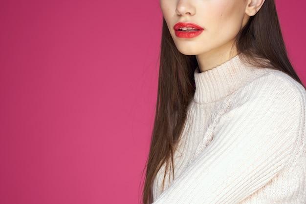 長い髪の赤い唇の化粧品の白いセーターピンクのクロップドビューのブルネット