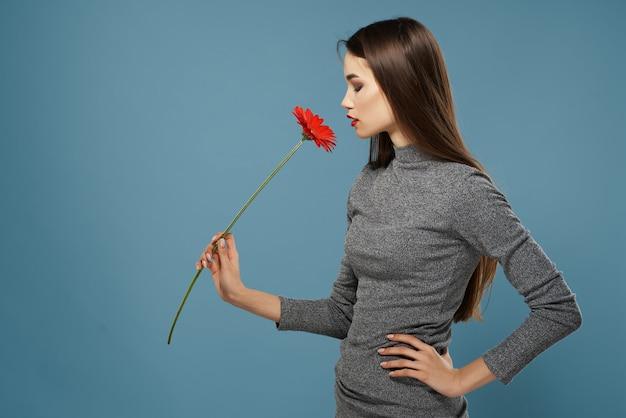 赤い花とブルネット明るいメイクグラマーロマンスのクローズアップ