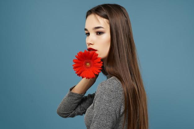 赤い花とブルネット明るいメイクグラマーロマンスのクローズアップ Premium写真