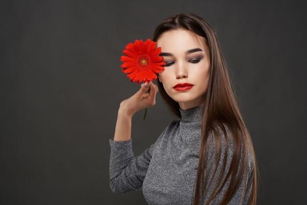 顔の高級化粧品のロマンスの近くに赤い花を持つブルネット。高品質の写真
