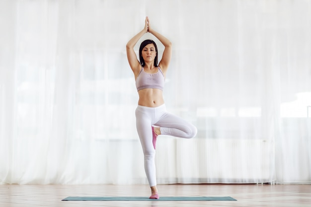 Brunette with short hair standing in tree with arms up yoga position. yoga studio interior.