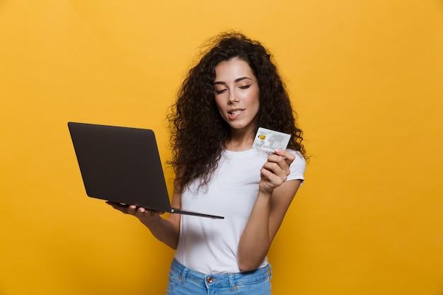 Брюнетка женщина 20 лет в повседневной одежде держит черный ноутбук и кредитную карту, изолированную на желтом