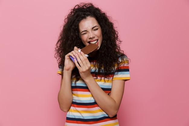 분홍색으로 격리된 초콜릿 바를 먹는 곱슬머리를 가진 20대 갈색 머리 여자