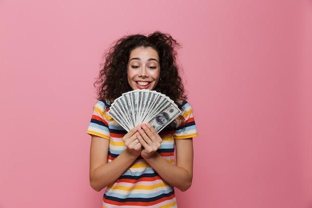ピンクに分離されたドルのお金のファンを保持している巻き毛のブルネットの女性20代