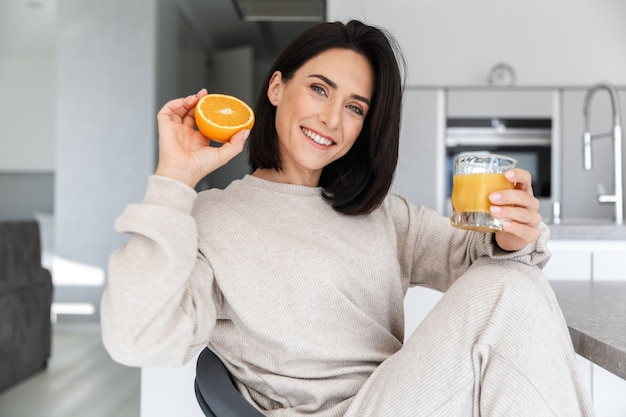 Brunette woman 30s drinking orange juice, while resting in bright modern room