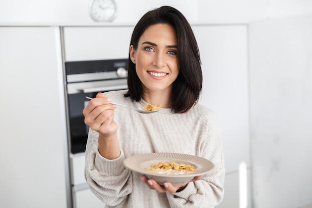 Брюнетка женщина 30 лет ест кукурузные хлопья на завтрак, стоя на современной кухне дома
