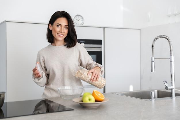 Брюнетка женщина 30 лет готовит завтрак с овсянкой и фруктами, стоя на современной кухне дома