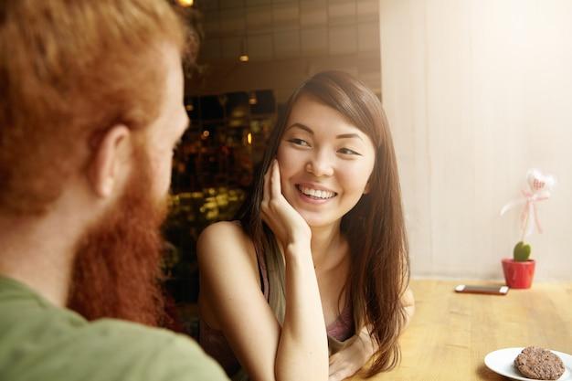 カフェに座っているブルネットの女性と生姜男