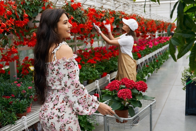 갈색 머리 여자와 꽃을 선택하는 젊은 노동자