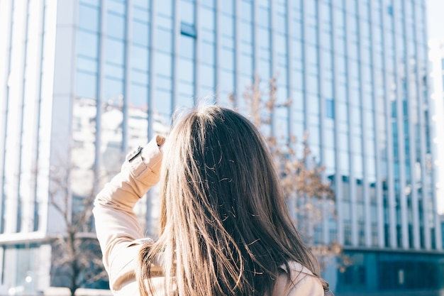 Brunette woman in beige coat looks at the high-rise building