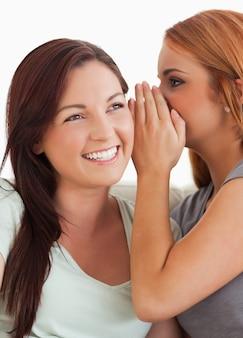 Brunette woman being told a secret
