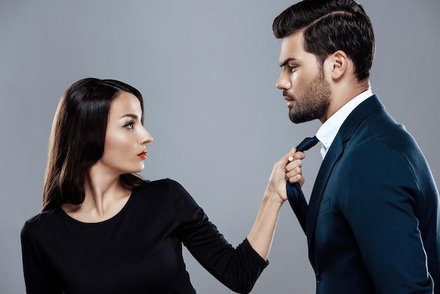 Brunette woman in black dress is holding stylish man by tie.