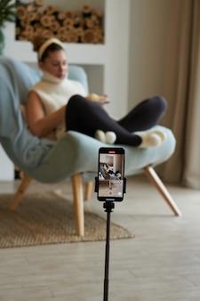 갈색 머리 여자 블로거가 집에서 스마트 폰 선택적 초점으로 자신의 사진을 찍습니다