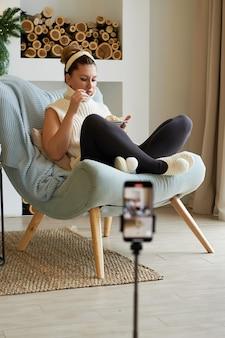 갈색 머리 여자 블로거가 집에서 스마트 폰으로 자신의 사진을 찍습니다.