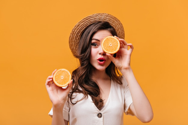 Brunette woman in boater is covering her eye with half orange and looking at camera against isolated background.