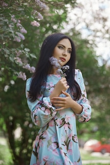 Brunette woman in the branches of a beautiful flowering tree