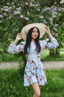 Brunette woman in the branches of a beautiful flowering tree.