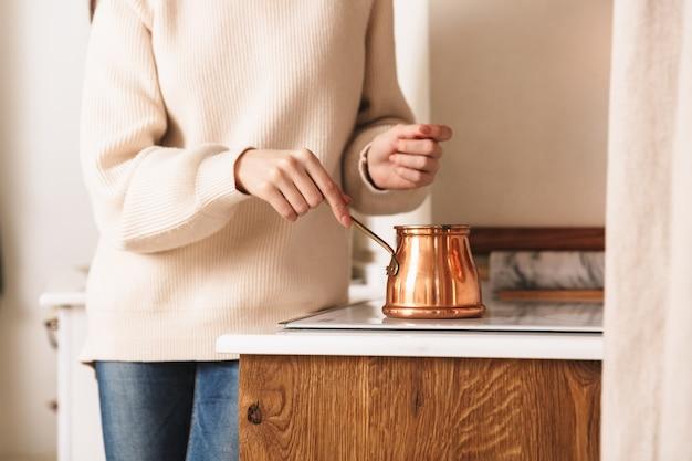 キッチンのプレートにステンレス鋼トルココーヒーポットでコーヒーを淹れるブルネットの女性