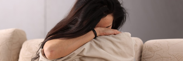 枕に頭を埋めるブルネットの女性。うつ病の概念を支援する