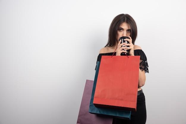 쇼핑백과 커피 컵을 들고 갈색 머리 여자입니다.