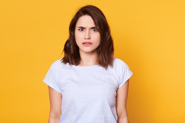 Brunette woman in casual clothes expressing disgust