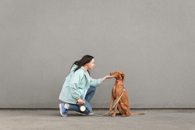 Brunette woman in casual clothing and dog on a leash sitting