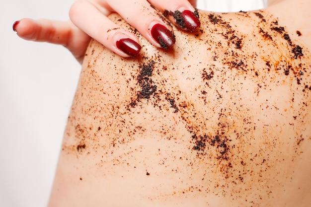 Брюнетка очищает тело кофейным скрабом