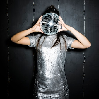 Brunette woman closing face by disco ball