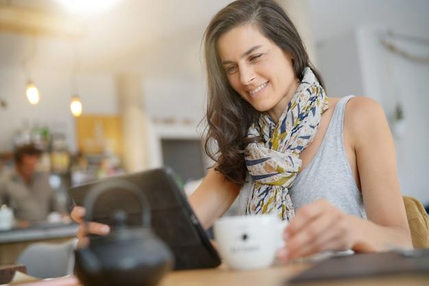 Brunette woman in coffee shop using digital tablet