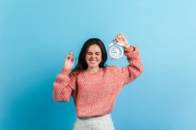 ブルネットの女性は彼女の指を交差させ、白い目覚まし時計を保持しています。青い壁にポーズをとる特大のセーターのモデル。